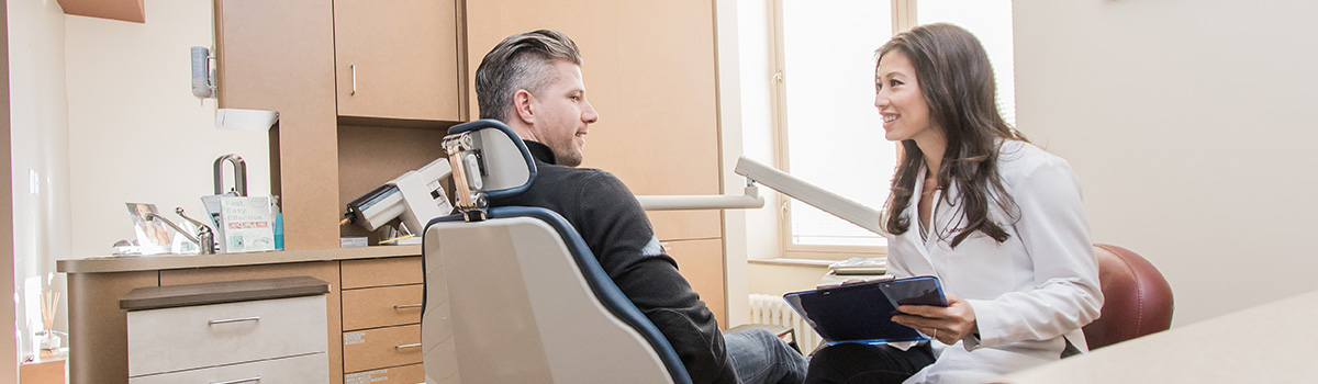 Dr. Vo sitting next to patient in dental chair